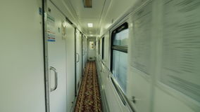 The interior of a passenger car on the road. The camera moves along the doors and windows of a comfortable car Steadicam. In the train car, a long corridor with stock video footage