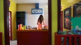 Interior of playroom in kids entertainment center. Girl playing in toy kitchen, cooking hamburger stock video footage