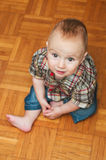 Interior portrait of a cute baby boy sitting on the wooden floor Royalty Free Stock Images