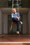 Interior, portrait of man grizzled. Guy hanging sitting on the chair, old industrial space background Royalty Free Stock Images