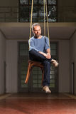Interior, portrait of man grizzled. Guy hanging sitting on the chair, old industrial space background Stock Photos