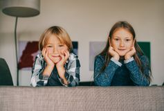 Interior portrait of two funny kids resting on the couch. Looking straight at the camera Royalty Free Stock Image