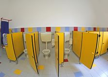 Interior of the school bathrooms with yellow doors without child royalty free stock photos