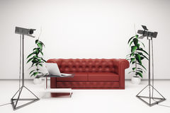 Interior with professional lighting equipment. Front view of bright interior with blank white wall, red leather sofa, laptop on coffee table and professional Royalty Free Stock Photos