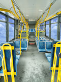 Interior of a public bus. The interior of a colourful public bus as viewed from the front to the rear Royalty Free Stock Image