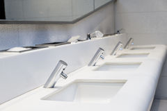 Interior of public toilet. Many faucet and sink in public toilet Royalty Free Stock Photography