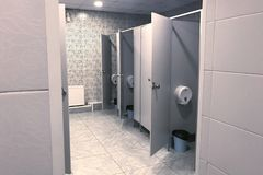 The interior of a public toilet with open doors stalls in gray tones. Side view royalty free stock photo