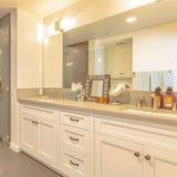 Interior quadrado do banheiro com o chuveiro separado da área da vaidade por uma porta de vidro foto de stock royalty free