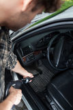 Interior que saca el polvo del hombre del coche Imagen de archivo