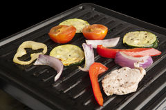 Interior raclette grill - Close up. Interior raclette grill with vegetables and meat - Close up Stock Photo