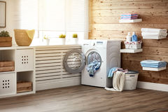 Interior of real laundry room with washing machine at window at