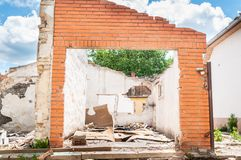 Interior remains of hurricane or earthquake disaster damage on ruined old house in the city with collapsed walls, roof and bricks. With selective focus stock images