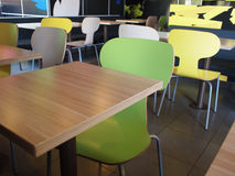 The interior of the restaurant fastfood. With bright colored chairs and empty tables without visitors Royalty Free Stock Images