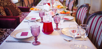 Interior of the restaurant, large table laid for Banquet, decorated in Burgundy tones Stock Photography
