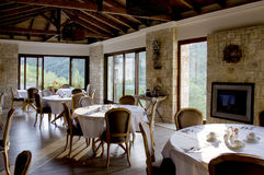 Interior of restaurant with wooden furniture and s. Interior of restaurant with wooden furniture ,stone walls and windows with view in forest Stock Photos