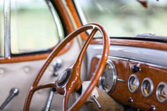 Interior retro car. Inside in a old car. Interior and dashboard detail of a restored retro soft-top British made classical car. Car 60's, 70's. The photo Stock Photo