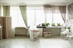 Interior in retro style bright room with a cot and large windows Stock Images