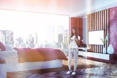 Interior rojo del dormitorio con TV, mujer fotografía de archivo