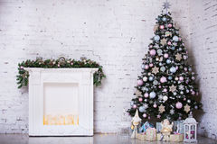 Interior room decorated in Christmas style. No people. Home comfort of modern house. Xmas tree and fireplace.  Royalty Free Stock Images