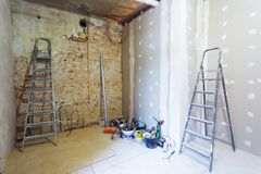 Interior of room during of install of plasterboard for making gypsum walls on the brick wall in an apartment is under. Ladders and construction tools and Stock Image