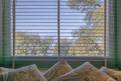 Interior Room Scene with Blinds and Pillows. Peaceful interior room scene with pillows and blinds showing blue sky and trees at Villa Ocampo, the home of the stock photo