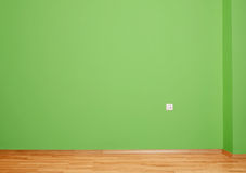 Interior room with wooden floor and wall in green with an electrical contact in the wall and wooden skirting Stock Images
