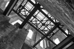 Interior of a ruined old industrial building, looking up at roof girders stock images