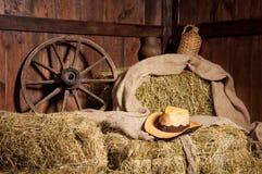 Interior of a rural farm - hay, wheel, cowboy hat Stock Photography