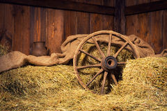 Interior of a rural farm - hay, wheel, pitcher Stock Image