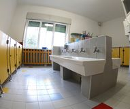 Interior of the school bathrooms with ceramic sinks and yellow d. Oors without children and a bright window stock photo