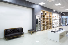 Interior of shoe store in modern european mall. Bright and fashionable interior of shoe store in modern mall Royalty Free Stock Photos