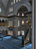 Interior shot of Nuruosmaniye Mosque with minbar platform, huge arches & colored stained glass windows, Istanbul, Turkey stock photography