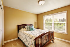 Interior simple del dormitorio con la cama de madera Fotografía de archivo