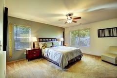 Interior simple del dormitorio con la cama y la silla Imagen de archivo