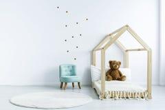 Interior simples da sala da criança com cama diy com um urso de peluche, armchai fotografia de stock