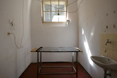 Interior of a small cramped room. Possibly a prison cell, with grungy hand basin and small table or desk below a window with bars royalty free stock image