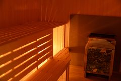 Interior of small home sauna. Warm light. Wooden benches royalty free stock image