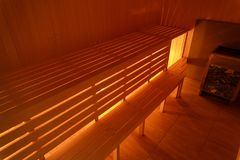 Interior of small home sauna. Warm light. Wooden benches royalty free stock images
