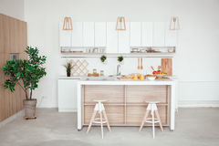 Interior of small white kitchen with fresh fruit, two glasses of orange juice, baguette, red caviar, croissant and. Cookies with chocolate chips on the table royalty free stock photography