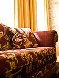 Interior with sofa. An interior of a room with a beautiful burgundy and gold sofa Stock Photo