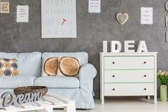 Interior with sofa and dresser. Cozy home interior with simple blue sofa, dresser and table royalty free stock photos
