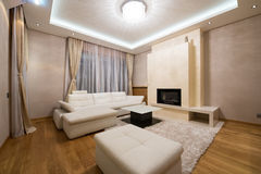 Interior of a specious living room with fireplace and luxury cei Royalty Free Stock Photo