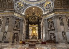 The interior of St. Peter`s Basilica in the Vatican. Baroque canopy over the altar, above the canopy rises a Department dedicated Stock Image