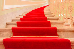Interior stairs with red carpet. Majestic interior marble stairs from a luxury building covered with  red carpet Royalty Free Stock Image