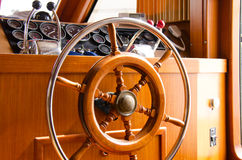 Interior steering wheel of large yacht boat. Wooden and metal steering wheel on the interior of a large yacht boat with gauges, engine throttle accelerators and Stock Photography