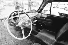 Interior and steering wheel on old vintage retro car. Black and Royalty Free Stock Photo