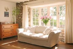 Interior of stone cottage. Living room of a stone cottage with stone walls and a dickens style bay window with flowers old fashioned type wall lights lit by the Stock Photo
