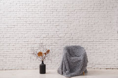 Interior in the style of minimalism. Chair and pot with dry branches against a white brick wall. Royalty Free Stock Photo