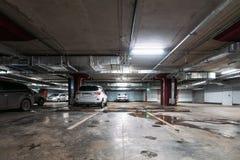 Interior subterrâneo iluminado da garagem de estacionamento do carro sob a alameda moderna com lotes dos veículos fotos de stock