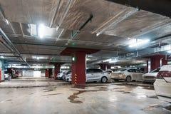 Interior subterrâneo iluminado da garagem de estacionamento do carro sob a alameda moderna com lotes dos veículos foto de stock royalty free